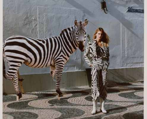 Model in zebra print clothing stands in front of a zebra.