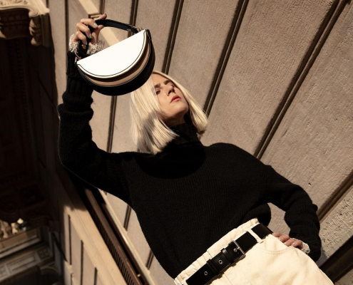 Model holds a Charles and Keith half-moon bag in black and white.