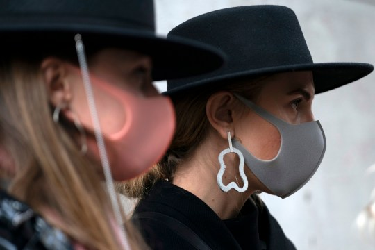 Two women at LFW wear masks
