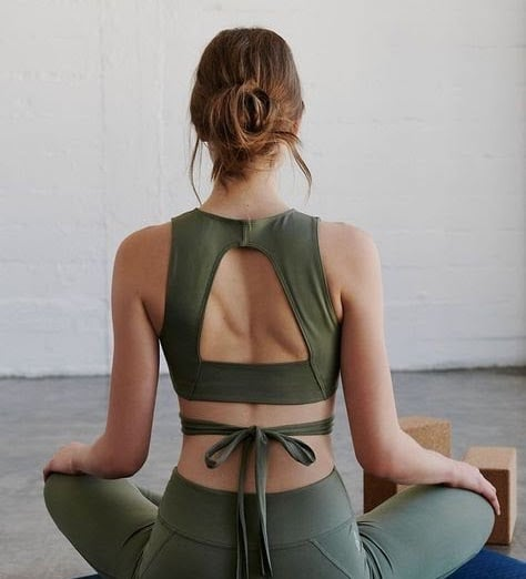 Woman meditates in khaki green activewear