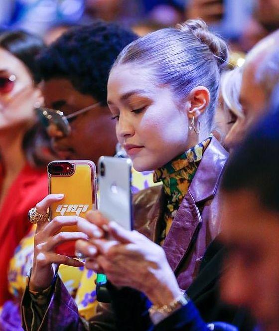 Model Gigi Hadid snaps a photo at a runway show