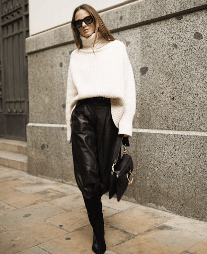 model poses in ribbed knit sweater and leather skirt