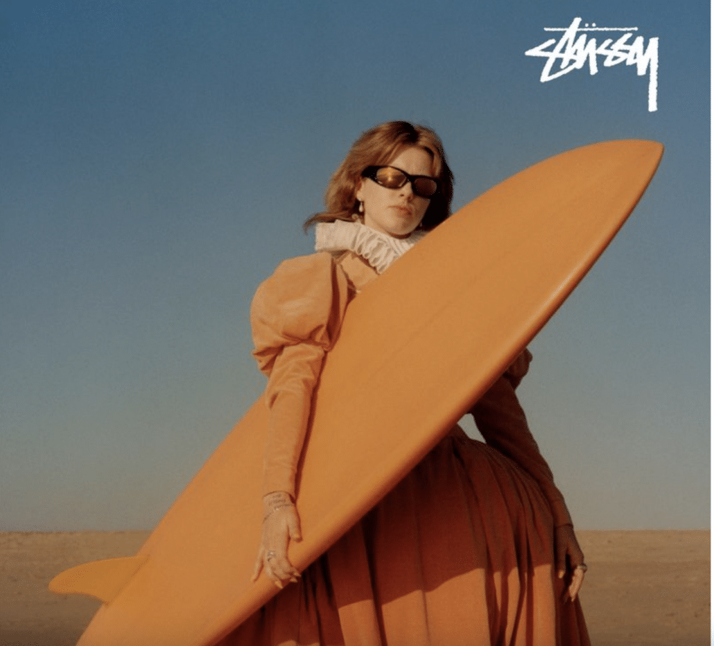 Model poses in Stussy dress with a surfboard on the beach