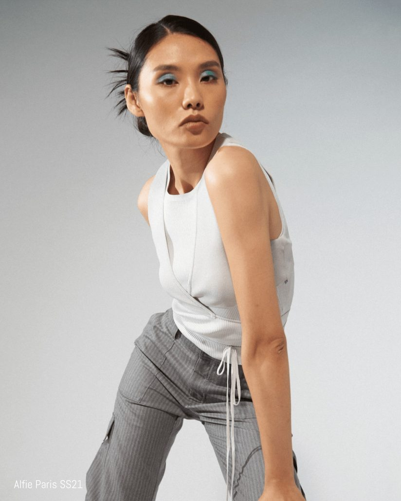 Model poses in pinstripe pants and a white tank top for Alfie Paris SS21