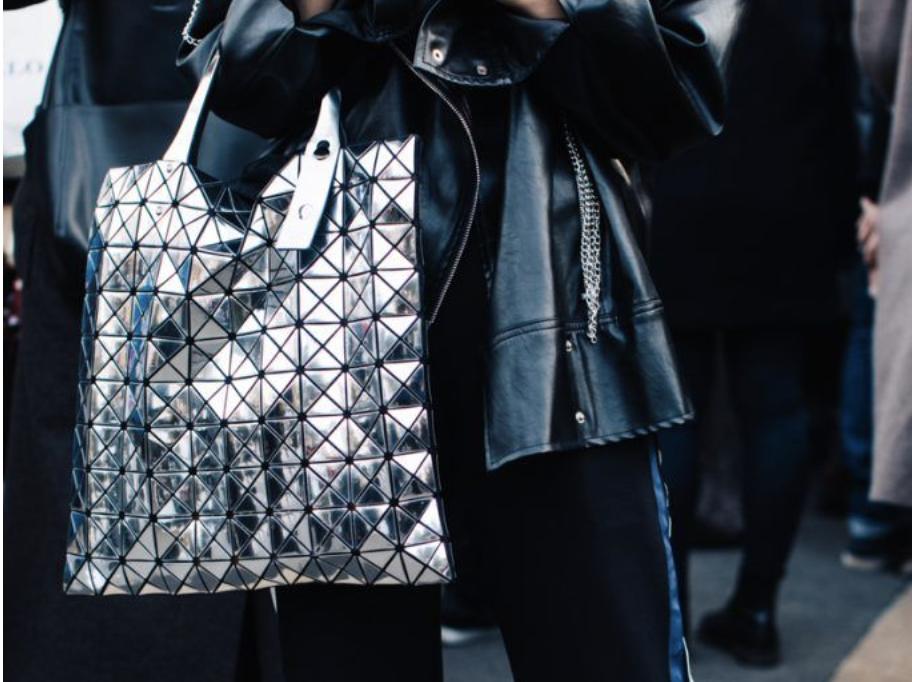 Streetstyler carries metallic shopping bag at Milan Fashion Week