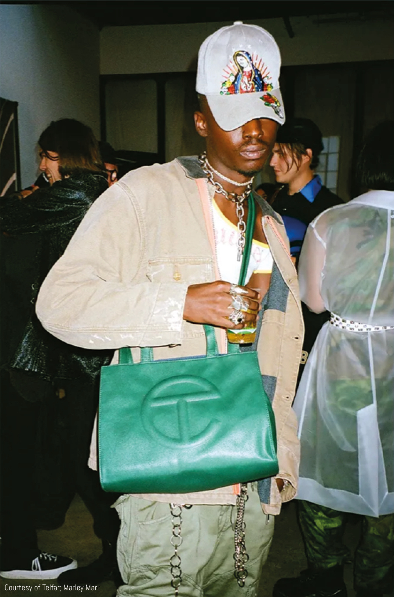 Model poses with green medium Telfar shopping bag
