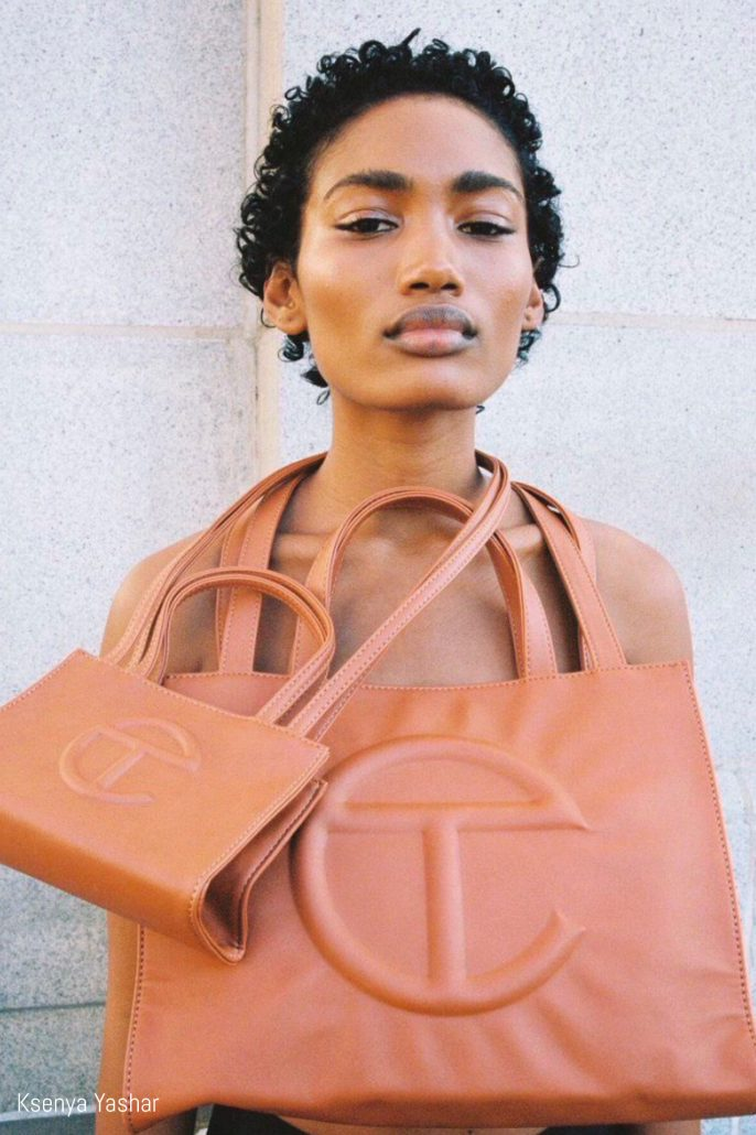 Model poses with two Telfar shopping bags around her neck