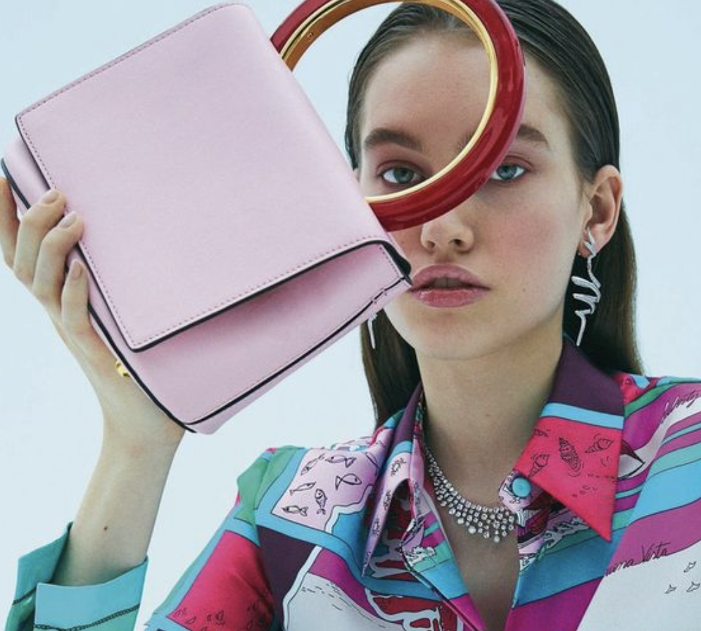 Model poses with pink purse shot by Emre Unal for Elle Turkey