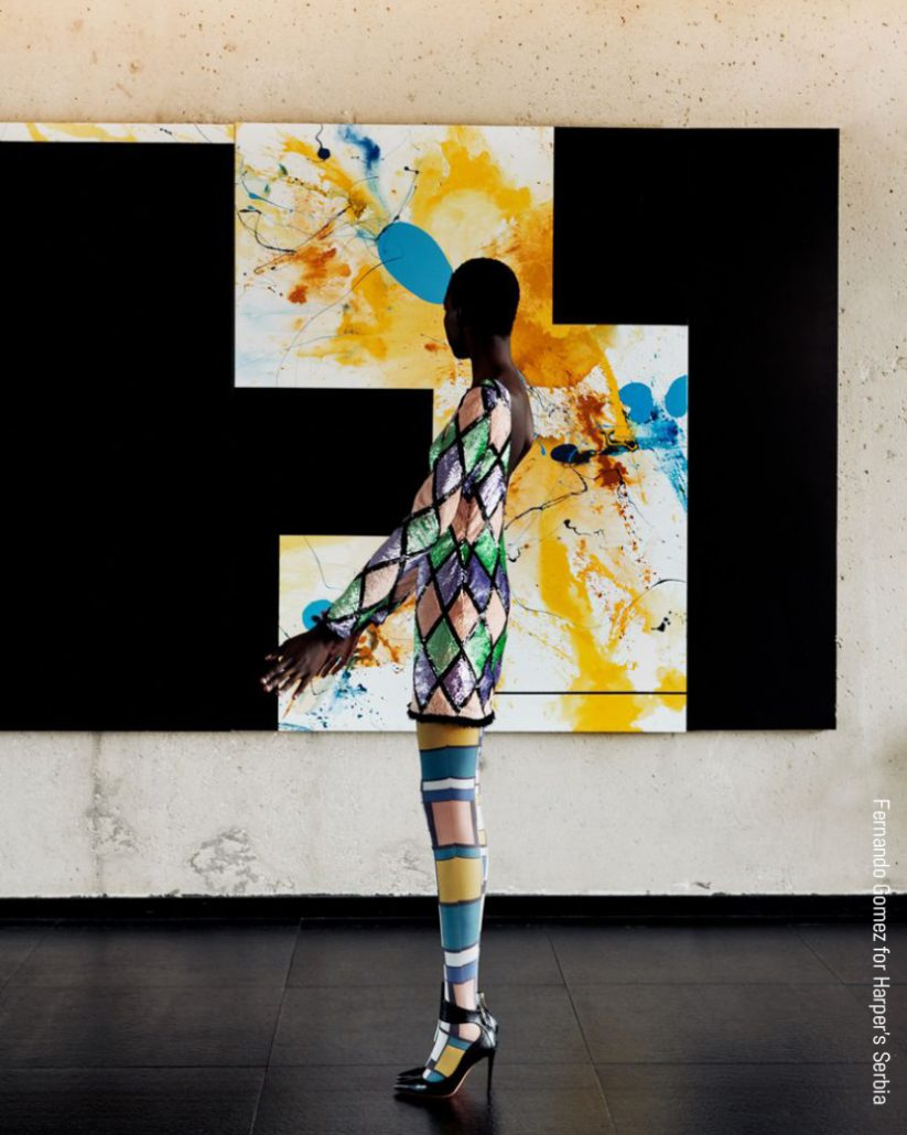 Models poses in bright colors in front of a painting