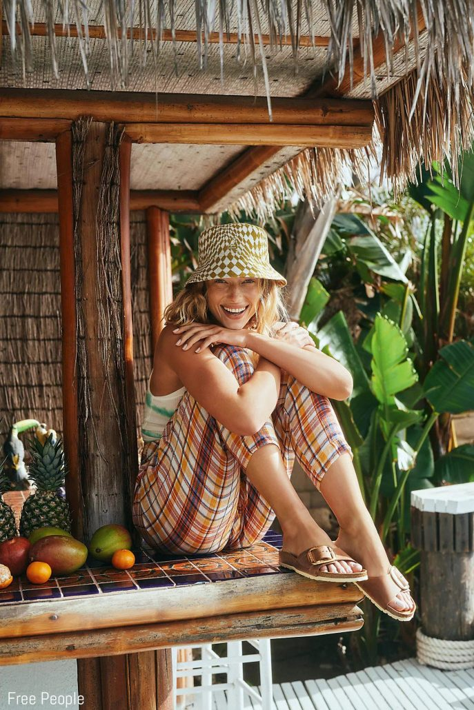 Models poses in a tiki hut for Free People
