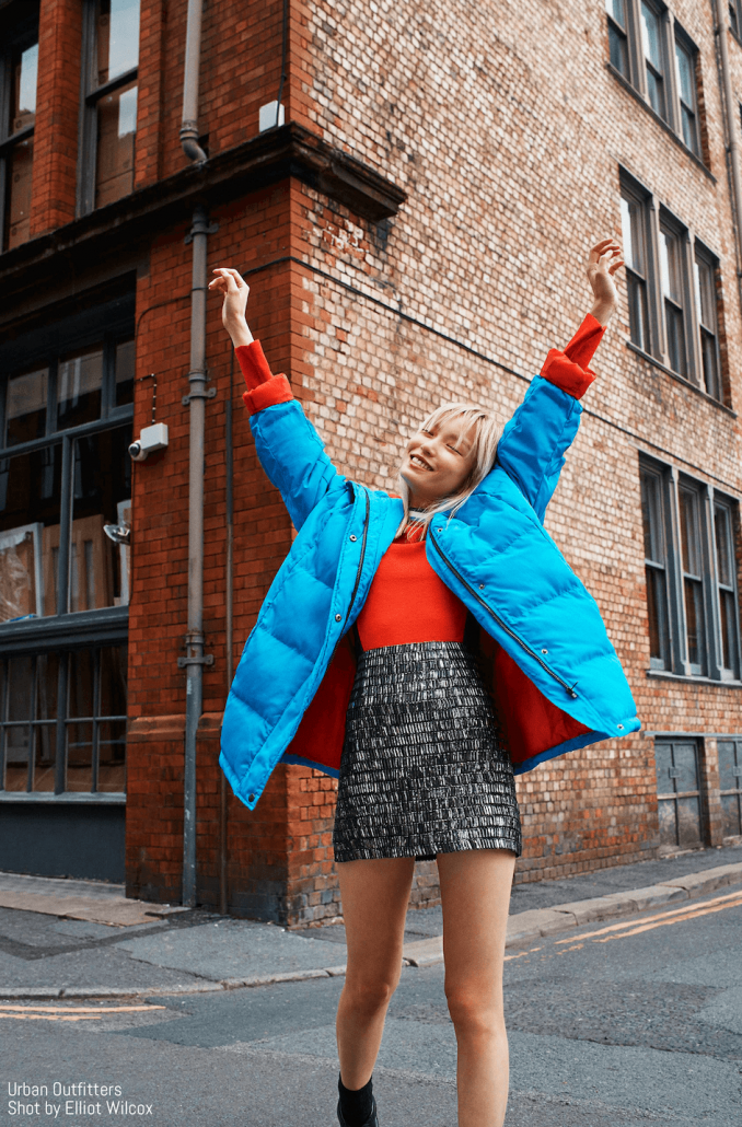 Model poses in puffer jacket and skirt for Urban Outfitters