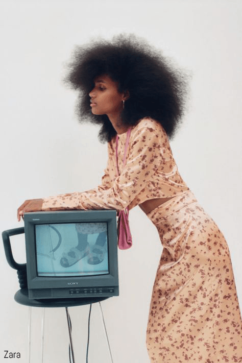 Girl poses in floral dress and leans on a TV for Zara campaign
