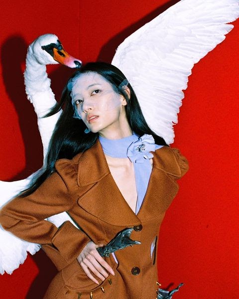 Model poses in a blazer with a swan for Louis Shengtao Chen
