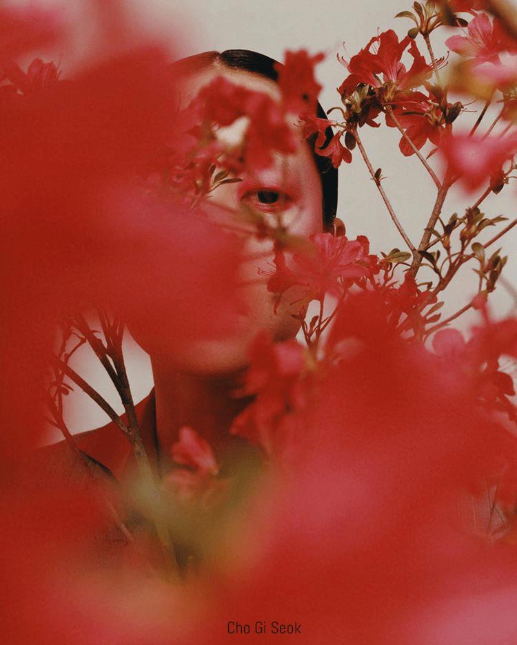 Model poses behind red flowers, shot by Cho Gi Soek