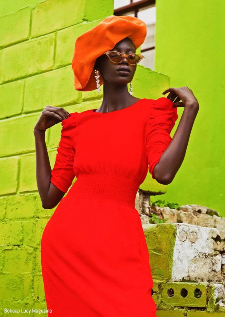 Model poses in orange beret and dress