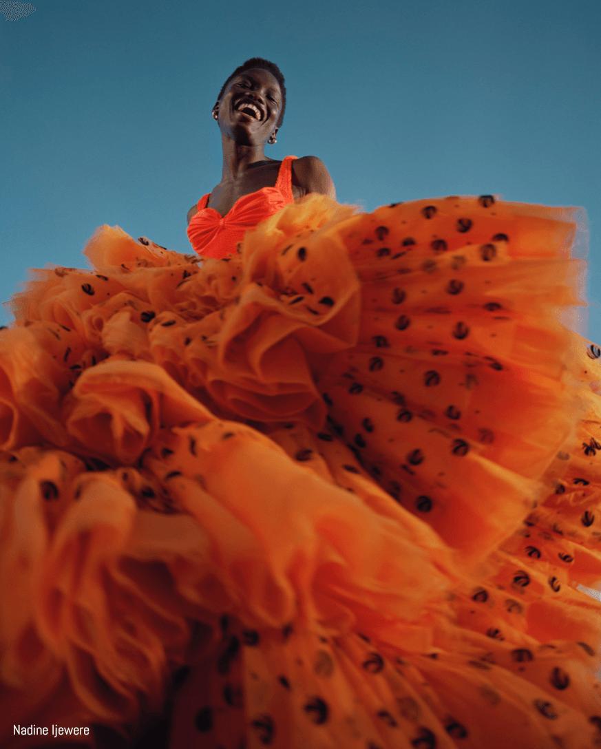 Model poses in orange tulle dress