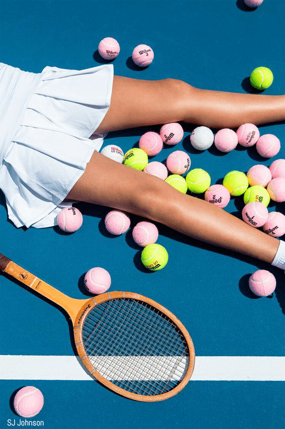 Girl in tennis skirt lays among tennis balls and a racket