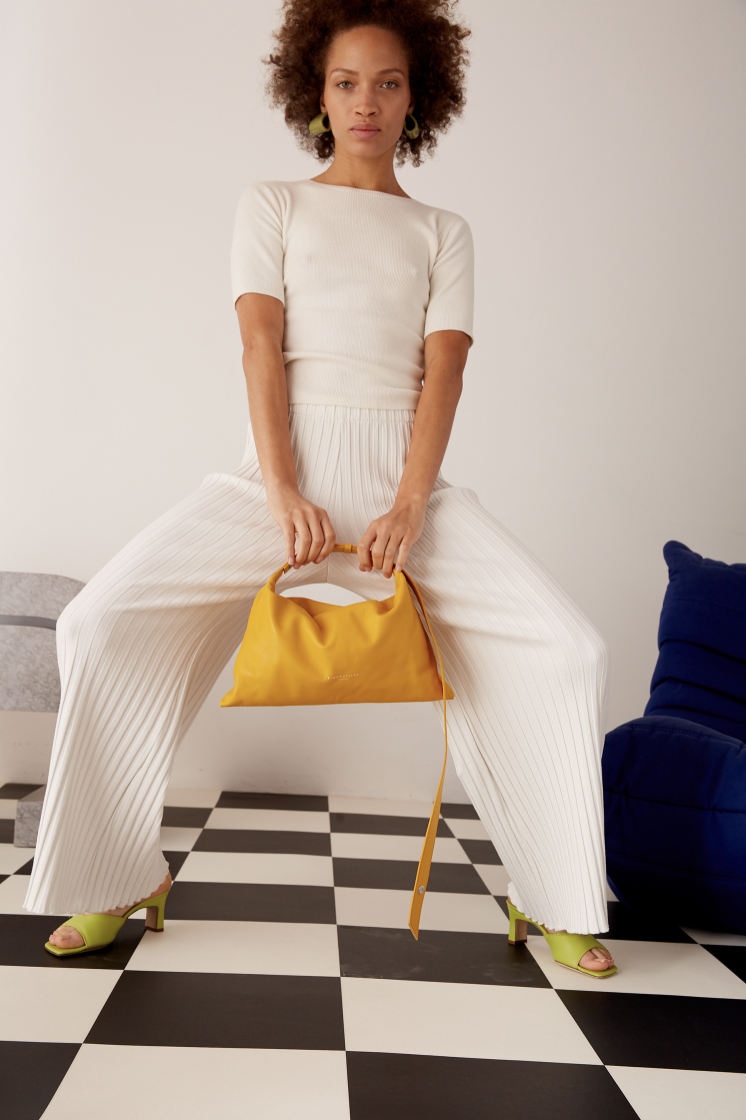 Model poses with yellow bag