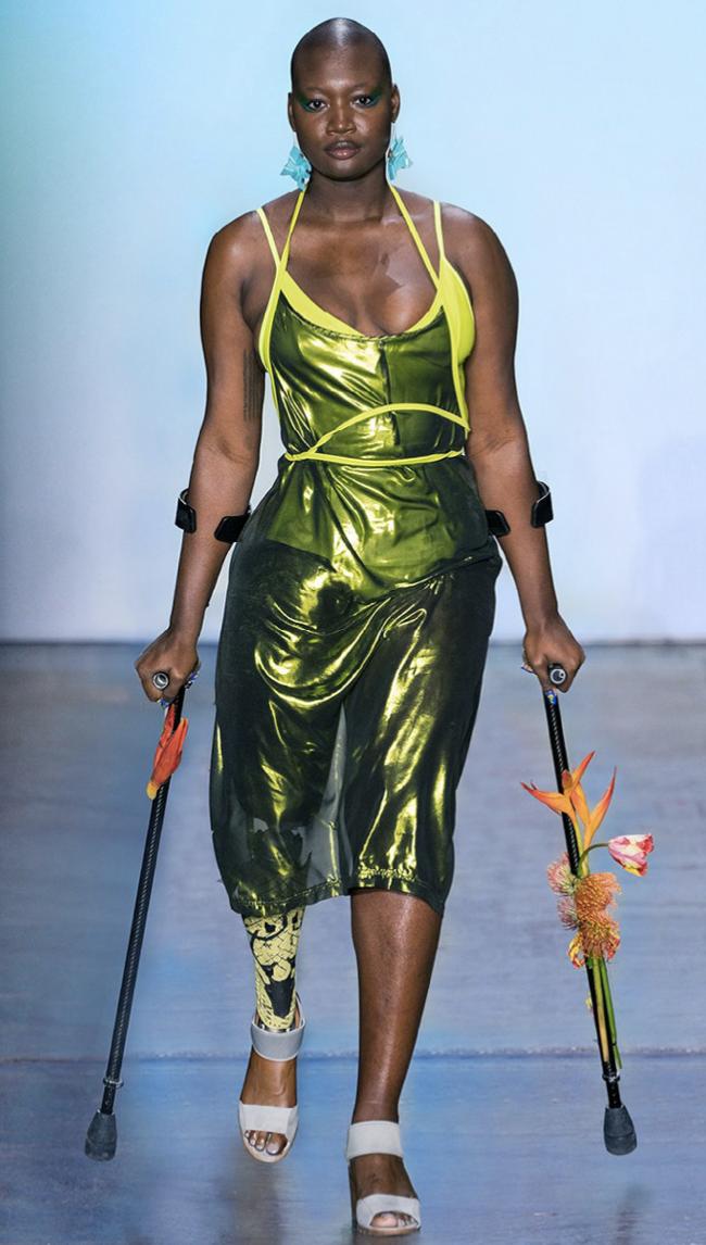 Model walks down runway in crutches